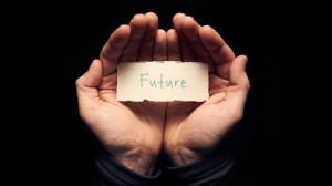 A man holding a card in cupped hands with a hand written message on it, Future.